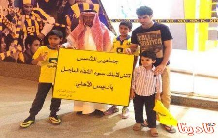 مشجع نصراوي يحمل لافتة كتب عليها دعوات لابن رئيس الأهلي